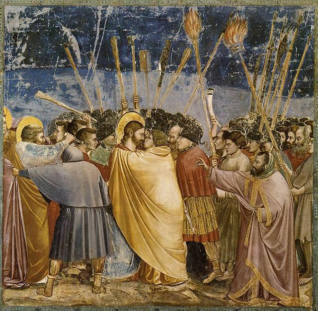 Il bacio di Giuda, secondo Giotto. Il mantello dell'Iscariota sembra di ottimo panno, abbondante e di un giallo segnaletico: indica l'unico ebreo tra romani fedeli al paganesimo, seguaci di Gesù e futuri convertiti.